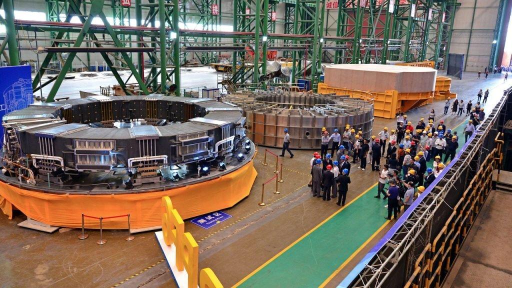 Для удержания плазмы в термоядерном реакторе ИТЭР нужно 25 сверхпроводниковых электромагнитов. Каждый из них — крупнейший в мире и весит 400 тонн. Диаметр — до 18 метров. На фото один из них находится слева, в центре — камера для его пропитки, справа — упаковка для транспортировки магнита. В сумме 25 магнитов весят десять тысяч тонн / ©tnenergy.livejournal.com