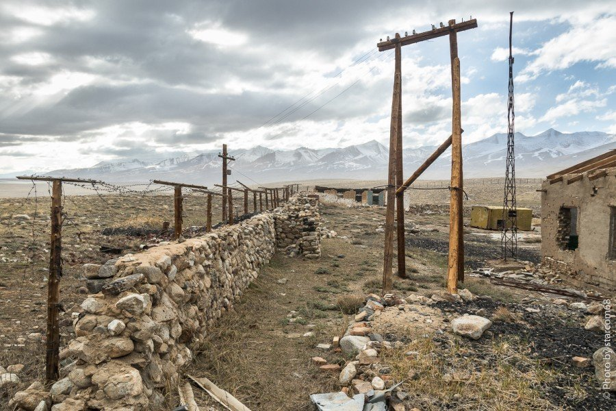 Ближе к углу казармы расположена антенна радиостанции и опора на которую сводятся провода от системы охраны периметра заставы.