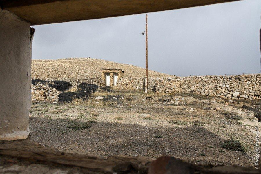 Вид из торцевого окна на чисто выбеленный изнутри туалет, оборонительную стенку и ближний угольный склад