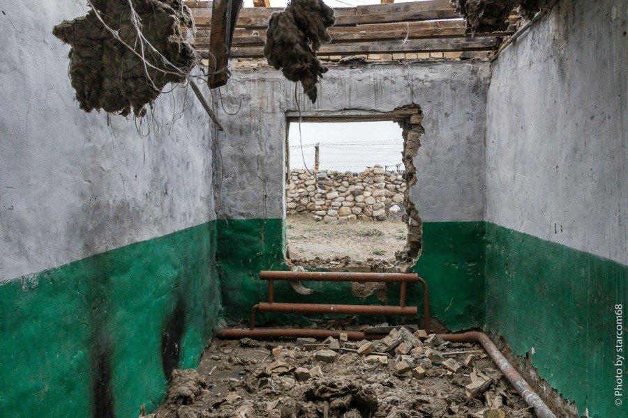 Помещение 2 с окном в сторону афганской границы.. С разобранного потолка свисают клочья стекловаты. Хорошо видно что стропила представляют собой не целые брусья и балки, а составные из чего попало.