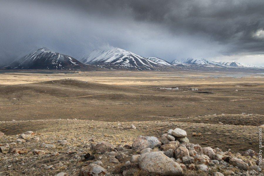 """Вид с правого борта долины реки Памир на пограничную заставу """"Зоркуль"""" и опорный пункт. На дальнем плане озеро Зоркуль и северные отроги Ваханского хребта. Граница с Афганистаном проходит от озера Зоркуль по отрогу с характерными полосами снега на месте осыпей"""